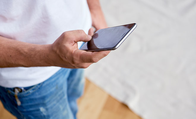 A paint contractor looks at his mobile phone