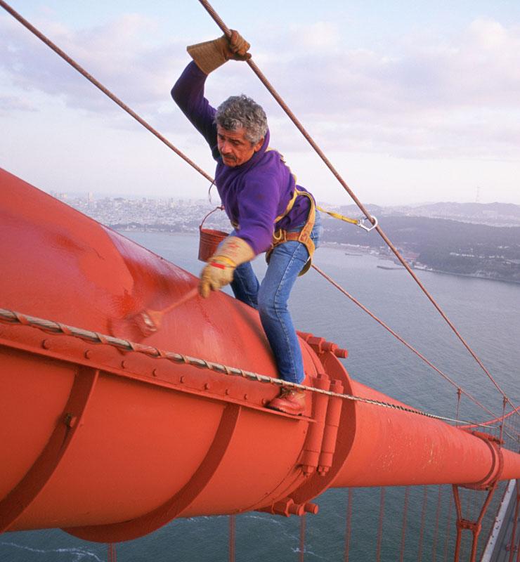 Un pintor aplica pintura roja en la parte superior de una torre del puente Golden Gate