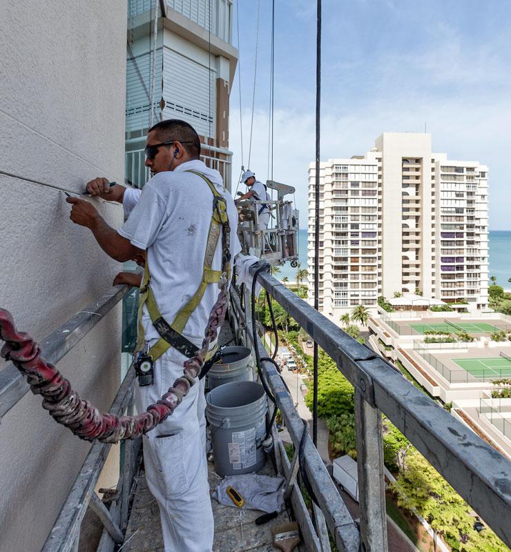 Un pintor parado sobre un andamio suspendido aplica pintura blanca al exterior de un edificio de piedra