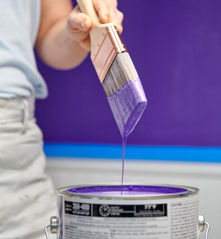 Un pintor sostiene una brocha después de sumergirla en un galón de pintura púrpura