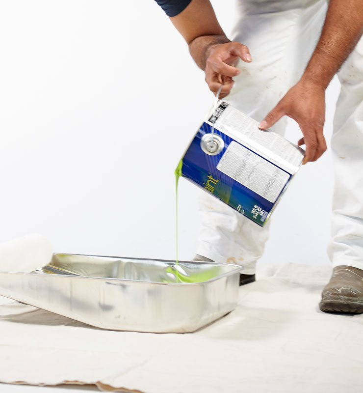Un hombre vierte pintura verde en una bandeja de metal de nueve pulgadas