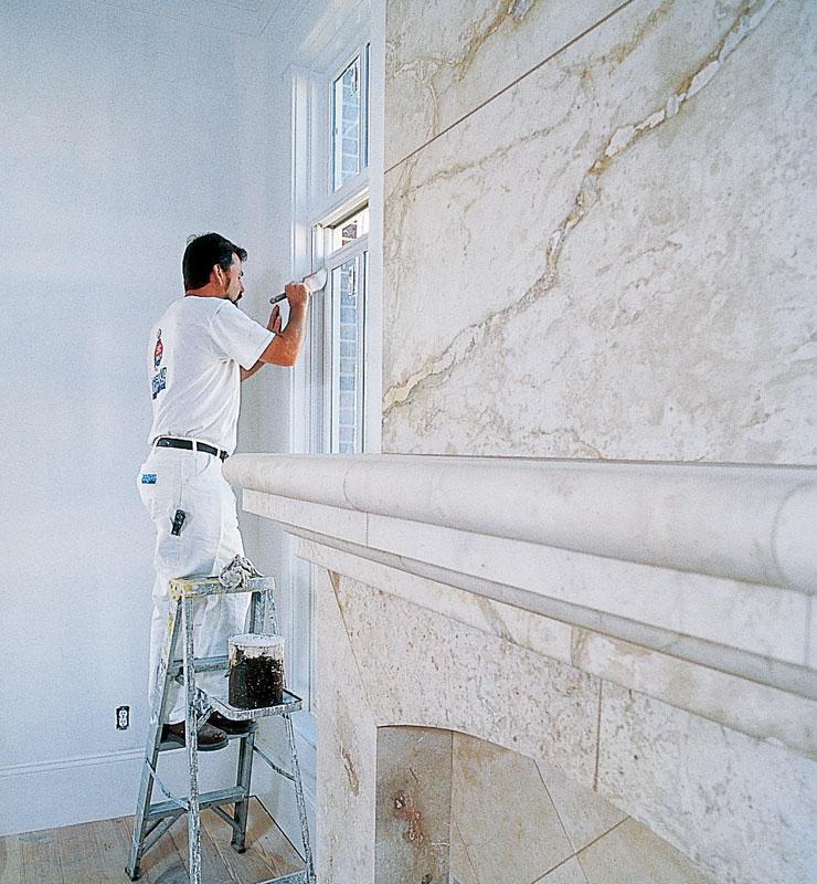 Un contratista de pintura aplica cuidadosamente pintura blanca con una brocha sobre un gran marco de ventana de madera