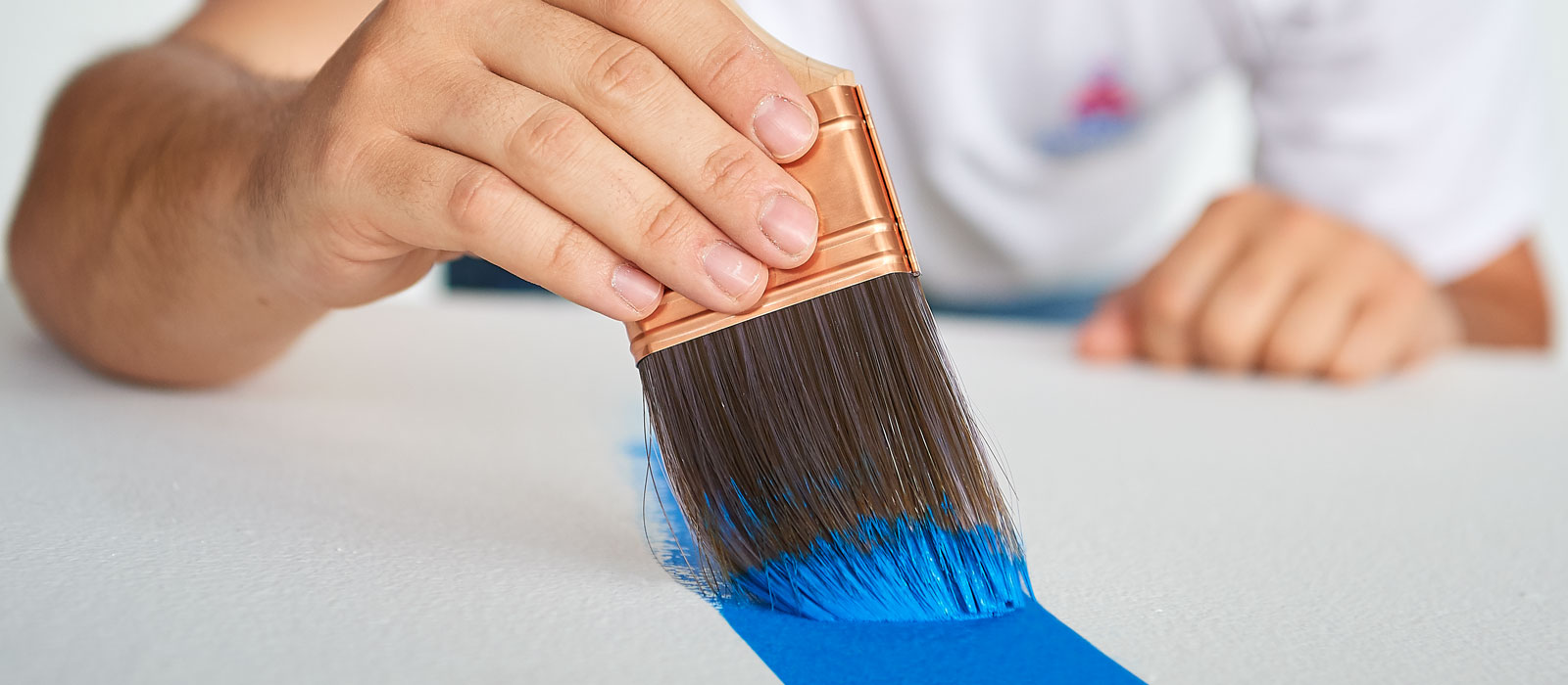 Low-angle close up: a painter's hand brushes blue paint onto a white surface.