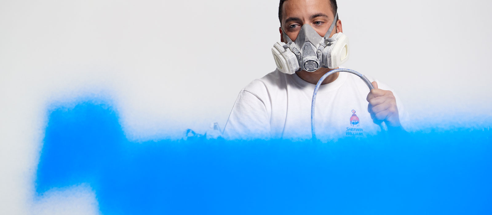 El pintor profesional Rob rocía una pared con pintura azul