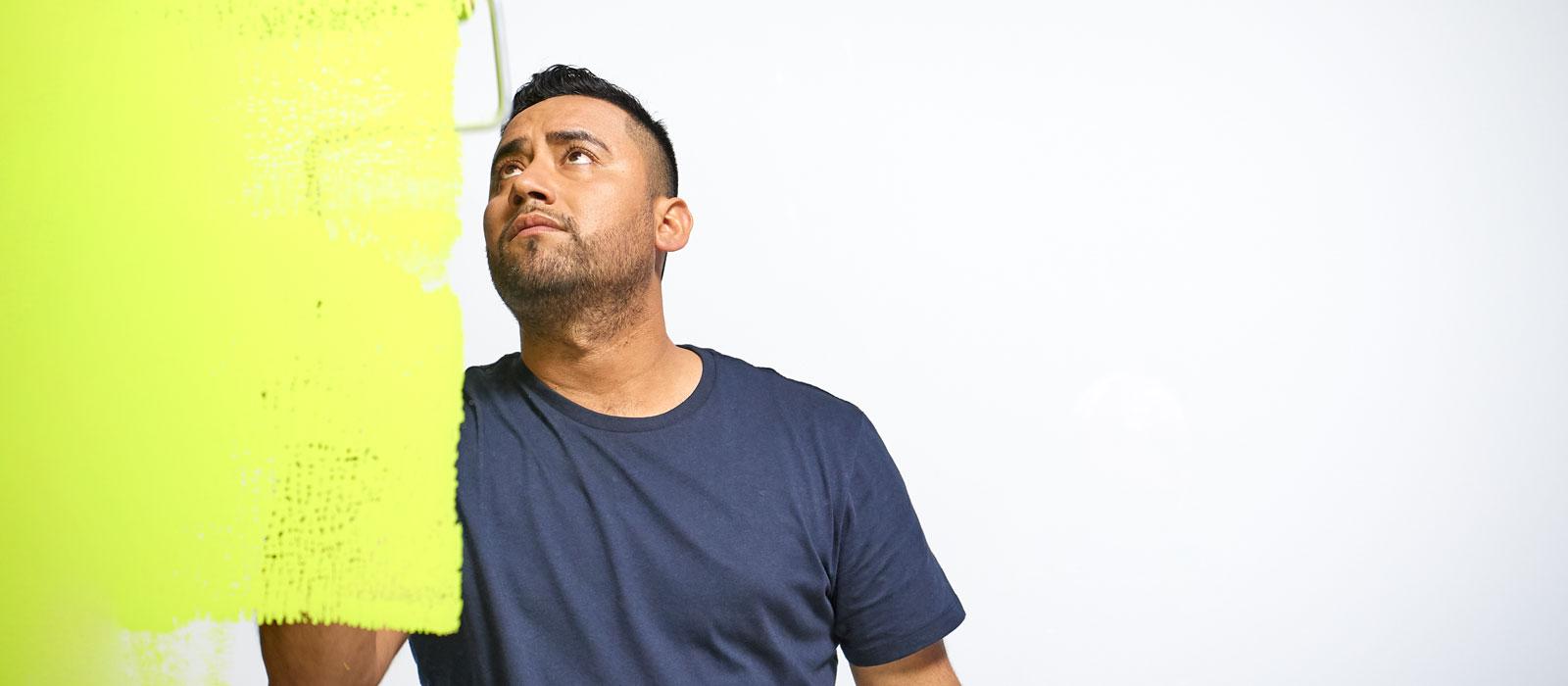 El pintor profesional Bernie aplica pintura verde con un rodillo en una pared