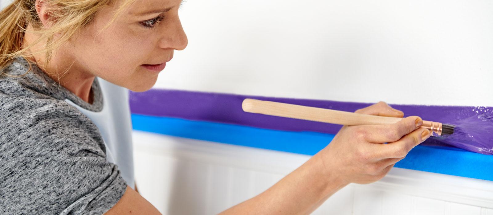 La pintora profesional Stephanie aplica pintura púrpura con una brocha en una pared sobre una guardasilla