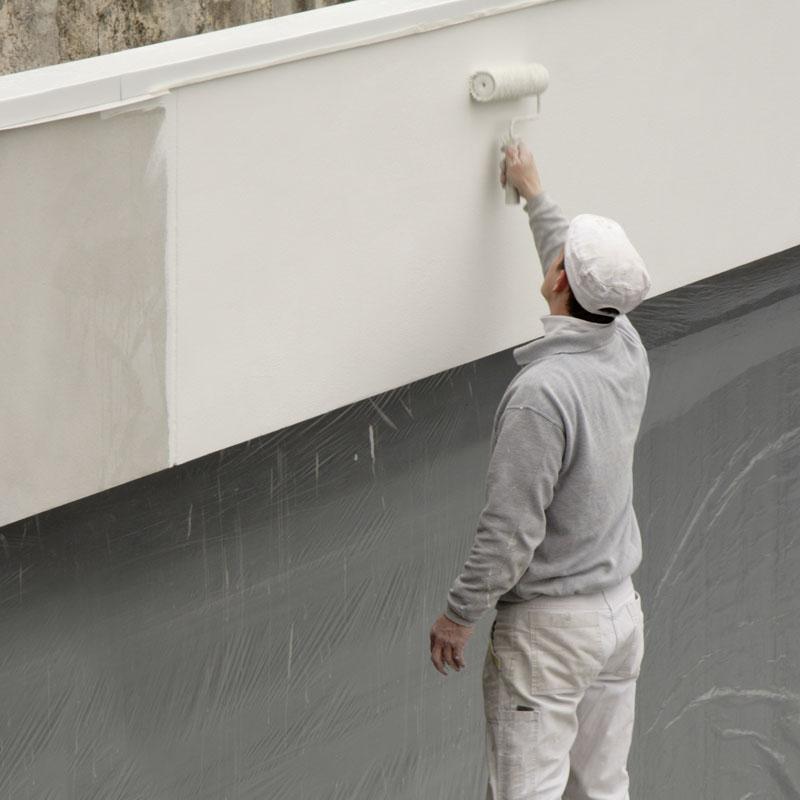 Un hombre pinta el exterior de un edificio comercial de color blanco utilizando un rodillo