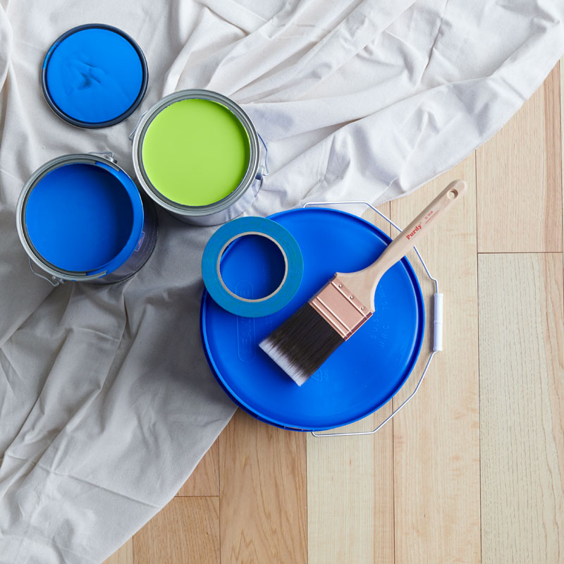 Dos latas de pintura abiertas se encuentran sobre una lona junto a una cubeta volteada que contiene una brocha y cinta de pintor